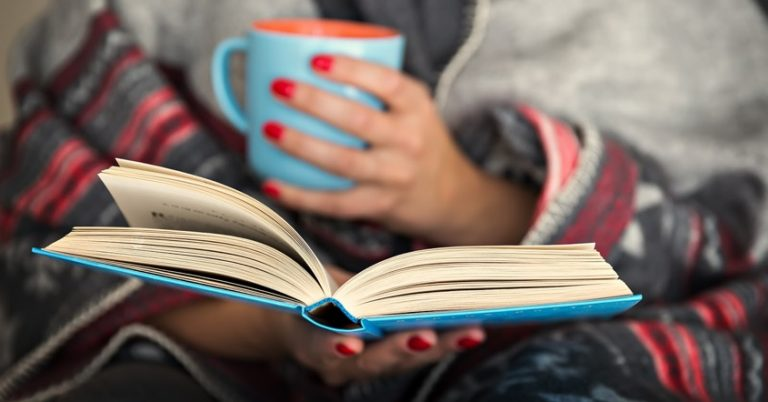 a woman wrapped in a blanket is holding a book open and holding a mug in her other hand