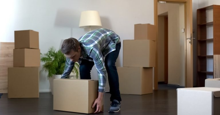 college student is bending over a cardboard moving box getting ready to pick it up