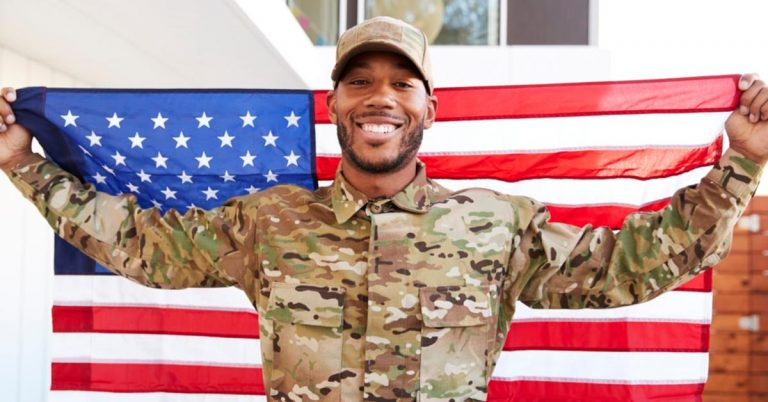 A man in a military uniform is smiling and holding an American Flag.