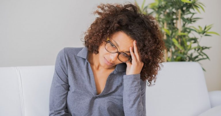 woman sitting on a couch is anxious and resting her forehead on her hand