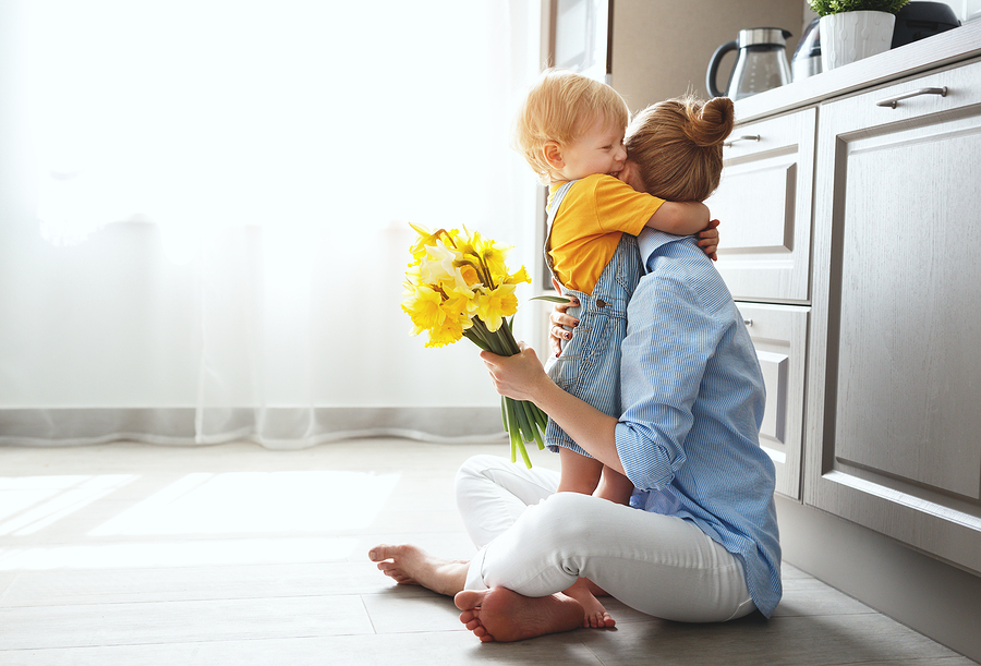 A woman hugs her toddler while sitting on the floor of a bright airy kitchen.