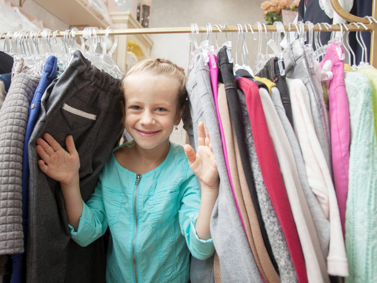 A girl peeking out of a rack of clothing at a resale shop.