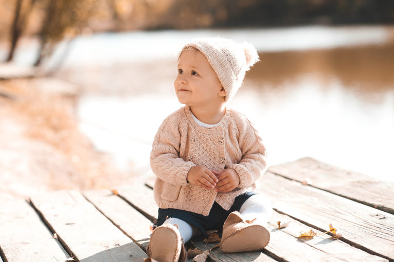 An adorable baby girl sits on a picnic table overlooking a lake.