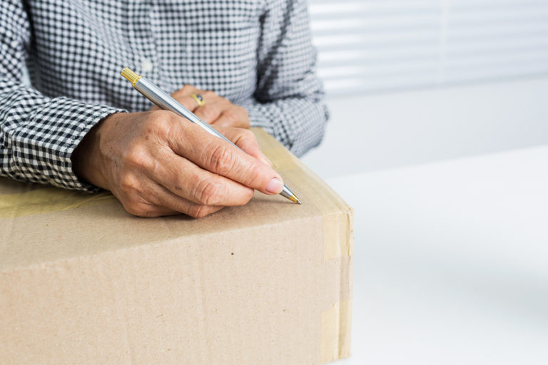 A man gets ready to label his storage box.