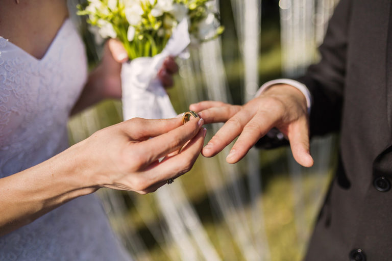 A close-up shot of a bride and groom exchanging rings.