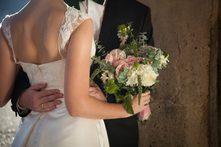 A bride and groom embrace against a rustic wooden backdrop
