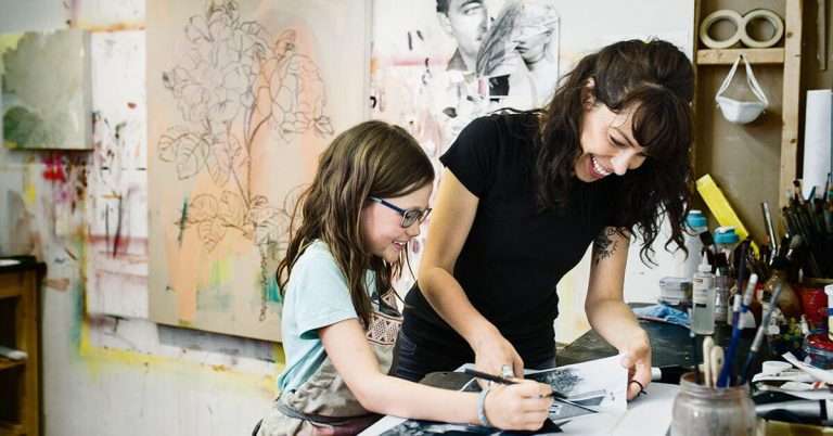A woman teaching a young girl how to draw.