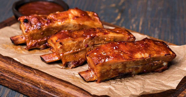 A platter of Columbia Missouri BBQ ribs lightly covered in BBQ sauce