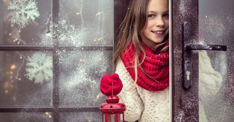A girl wearing festive clothing peeks from a winter and is holding a lantern