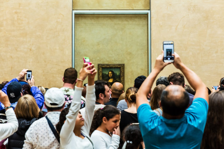"""A crowd of people stand in front of the """"Mona Lisa"""""""