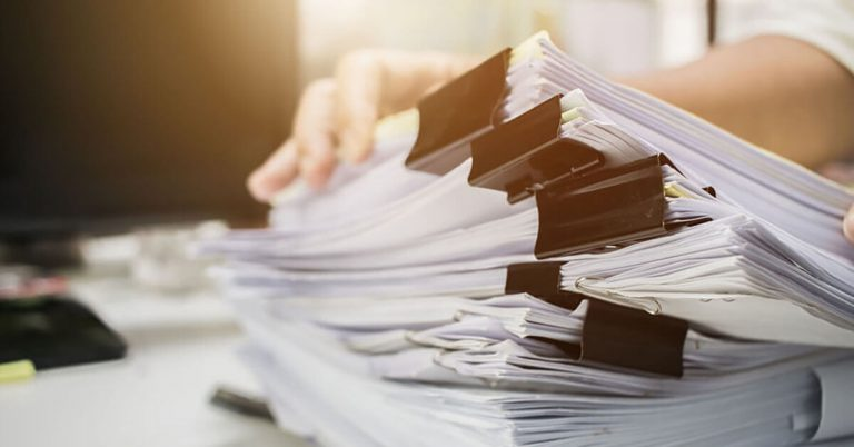 A businessman holds a stack of papers.