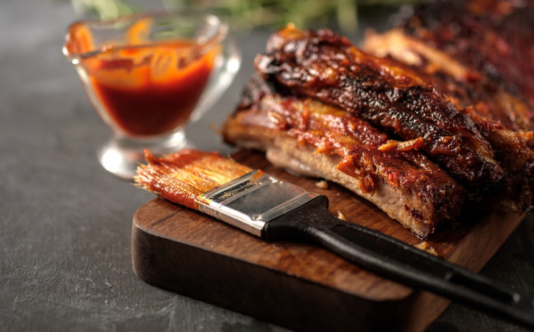 A platter of cooked ribs next to a bowl of barbecue sauce and a basting brush