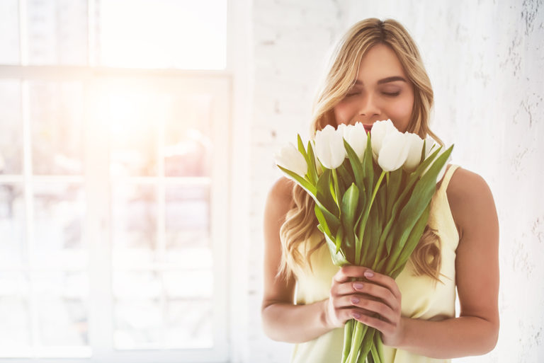 A woman smelling white flowers.