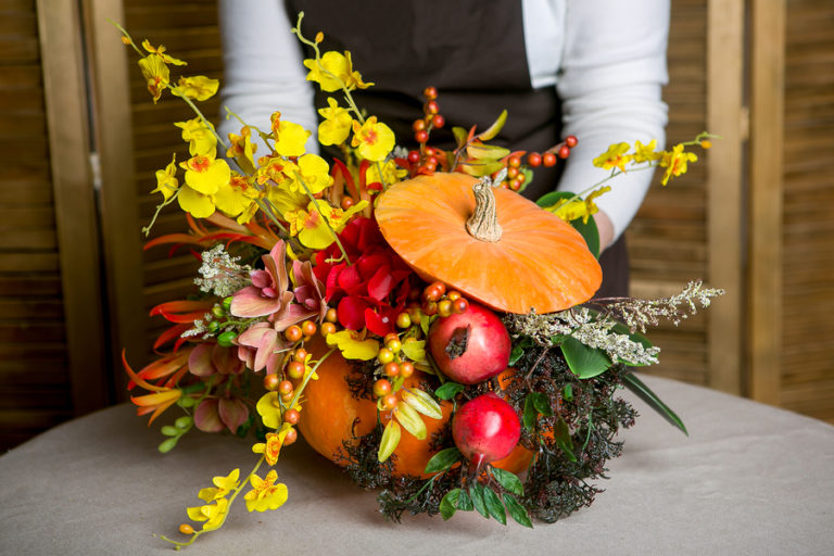 A woman puts the finishing touches on a floral centerpiece made using a carved pumpkin.