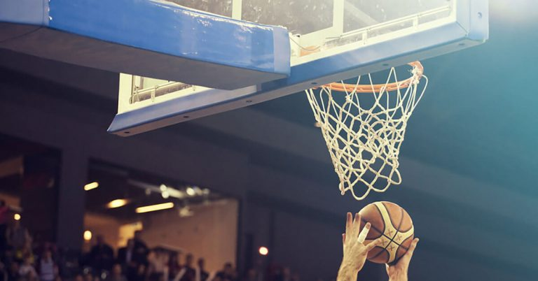 A close up shot of hands about to dunk a basketball.