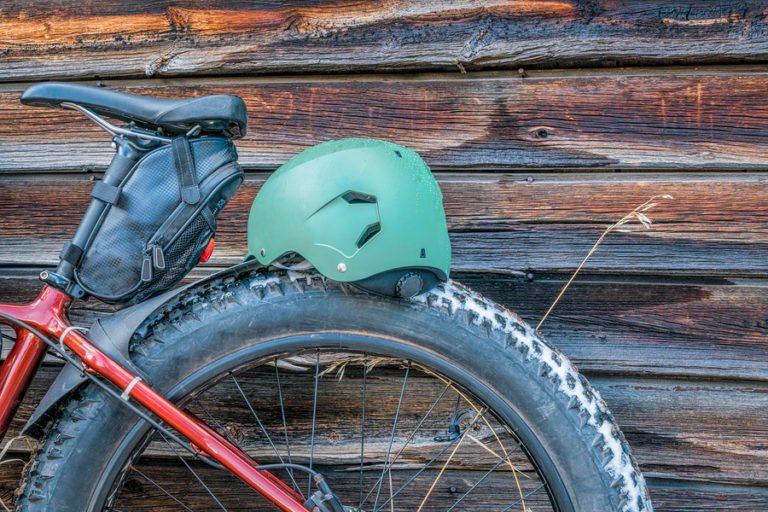 A red bike with a saddle bag on it rests against the side of a wood cabin.