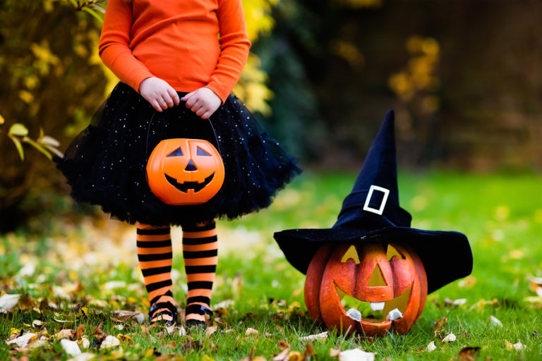A little girl wearing orange and black stands next to a carved pumpkin.