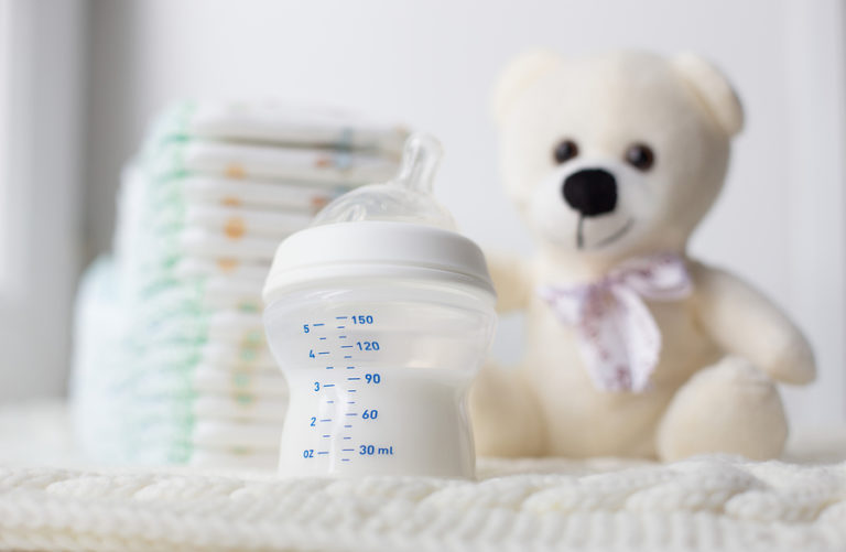 A teddy bear and baby bottle with diapers.