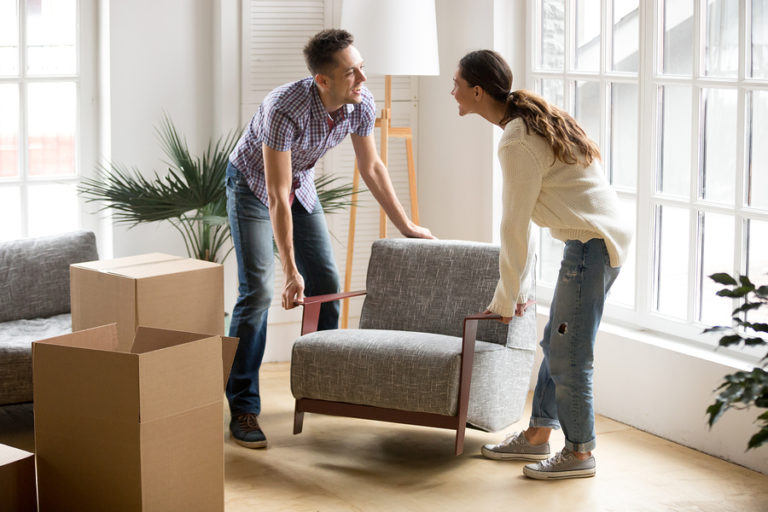 A young couple arranges a new chair in their house.