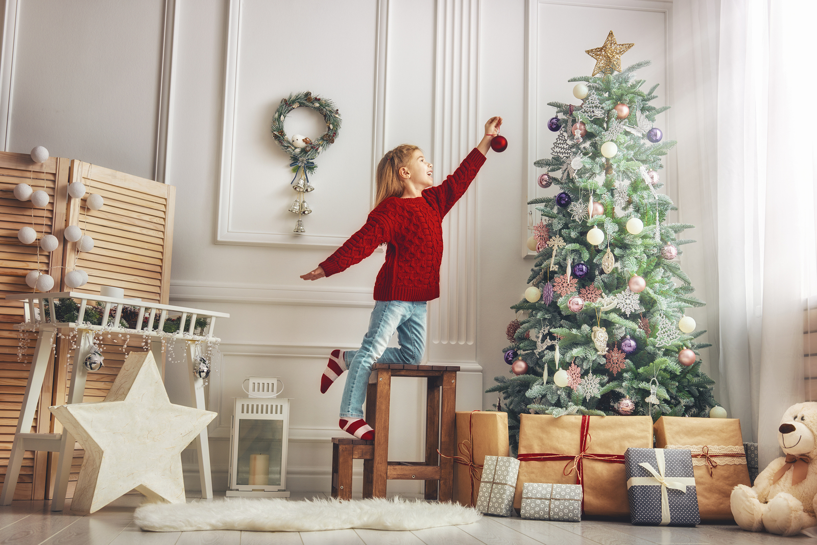A young girl places an ornament on a Christmas tree.