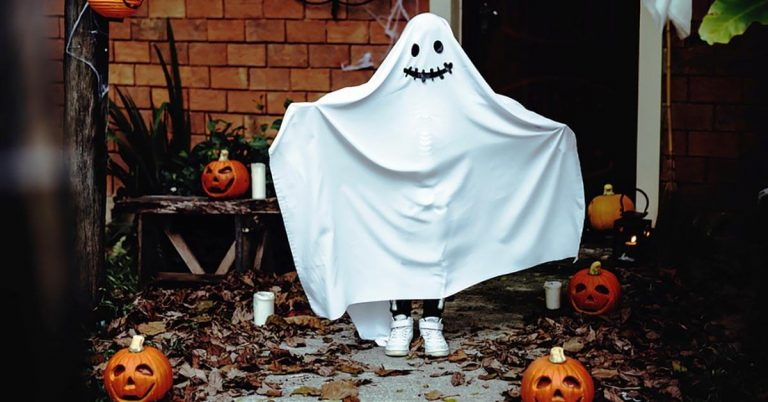 A child is dressed up for Halloween as a ghost.