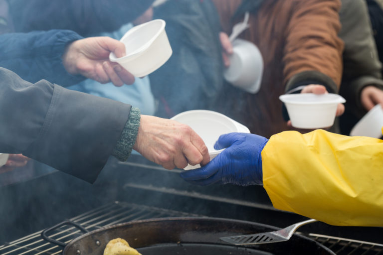 A volunteer gives out food to a group of homeless people.