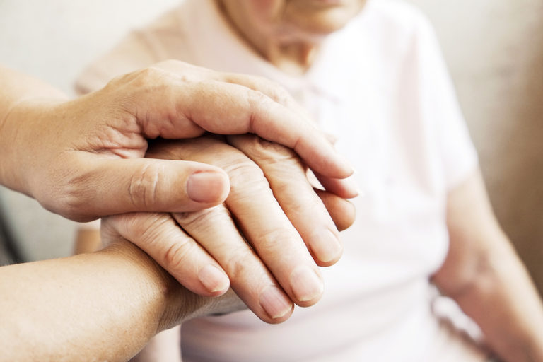 An elderly couple holds hands.