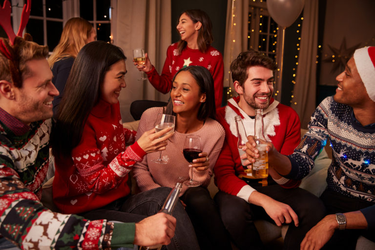 A woman in a red sweater hosts a holiday party in her small apartment.