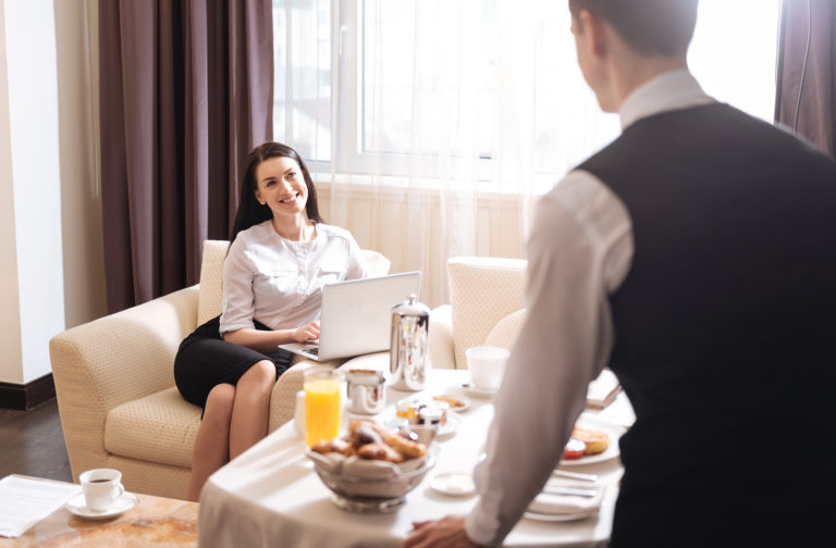 A businesswoman orders room service in a hotel room.