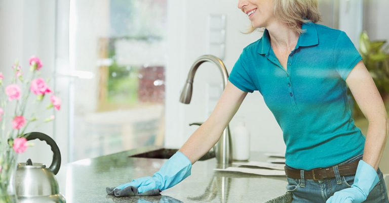 Woman cleaning the kitchen in her house.