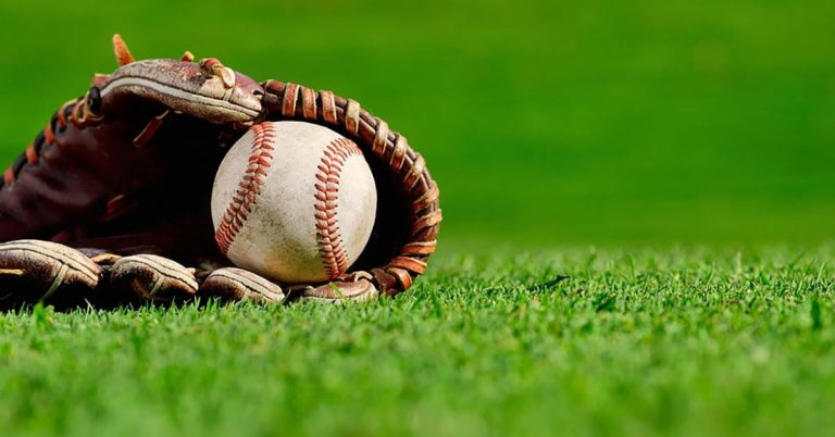 A baseball glove sitting on the grass with a baseball inside it.