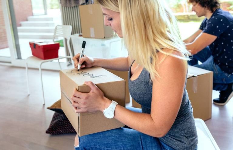 A blonde woman uses a black marker to label a cardboard box.