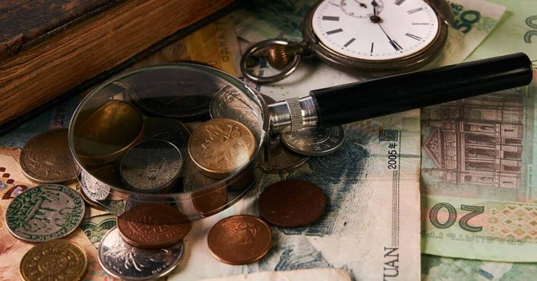 A collection of coins and foreign paper money sit on a table next to a magnifying glass.