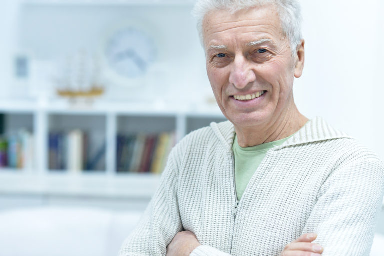 A happy older man smiles while standing in his organized home.