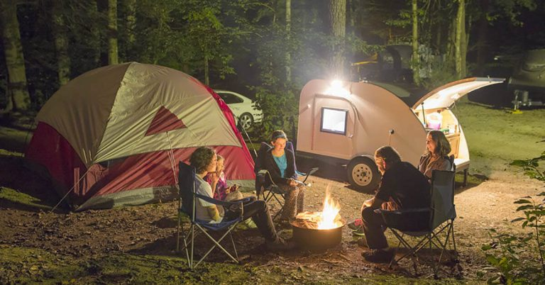 A family of five gathers around a campfire