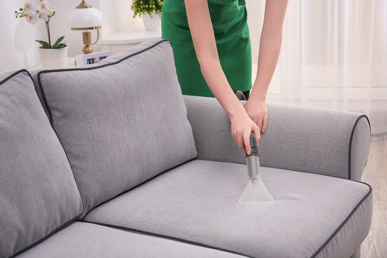 A woman vacuums her couch.
