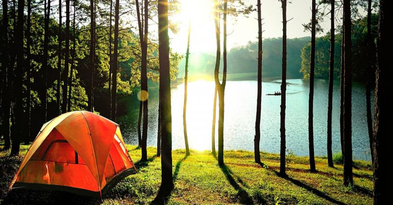 A bright orange tent is pitched at the edge of a lake