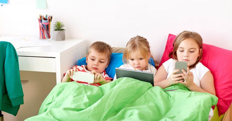 Three young kids in bed with phones and tablets.