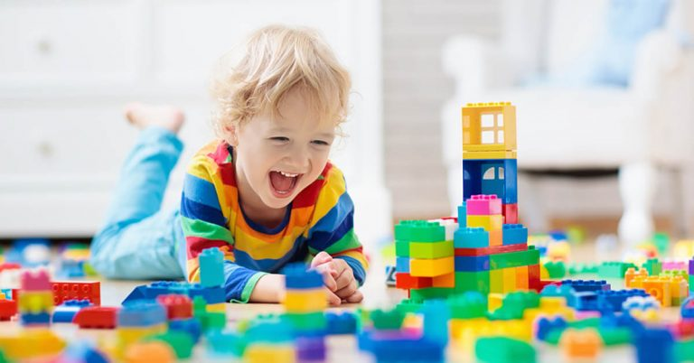 A young boy plays with building blocks.