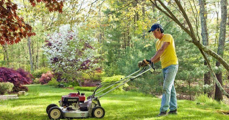 A man mowing his lawn during a sunny summer day.