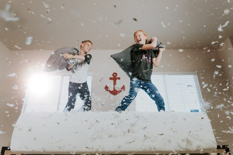 A brother and sister have an epic pillow fight on a full-size mattress