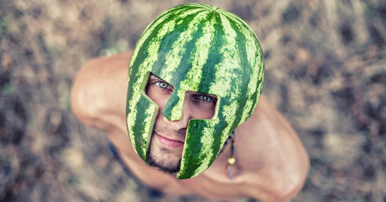 A man wears a helmet made out of a watermelon.