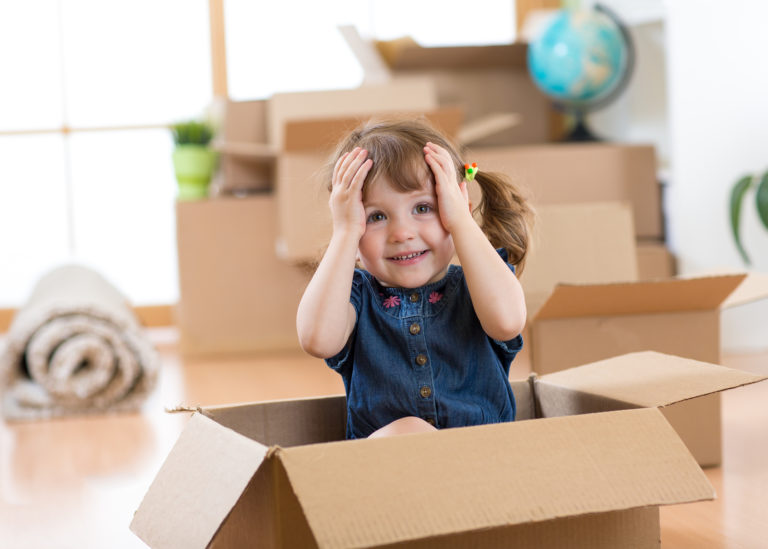 A cute little girl peeks out of a moving box in the home she has just moved into.