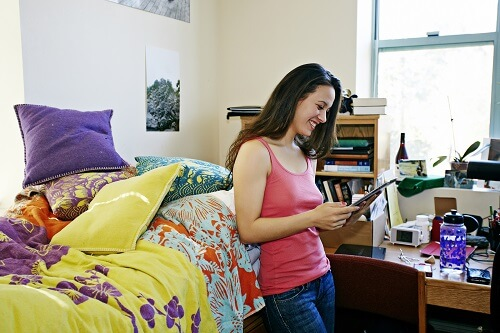 A young college student uses her iPad to find dorm organization tips.