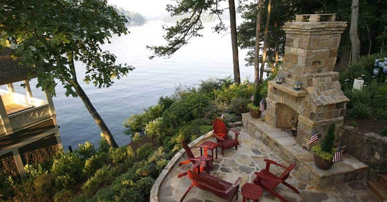 An outdoor fireplace sits on a patio overlooking the lake.