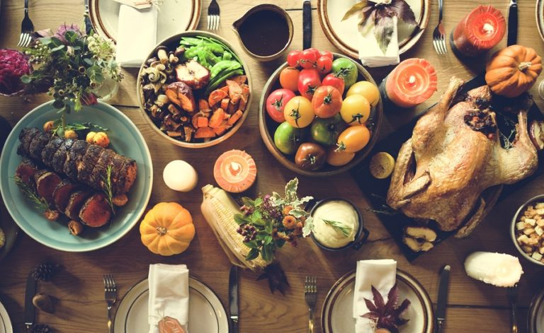 A dinner table is covered with a Thanksgiving feast