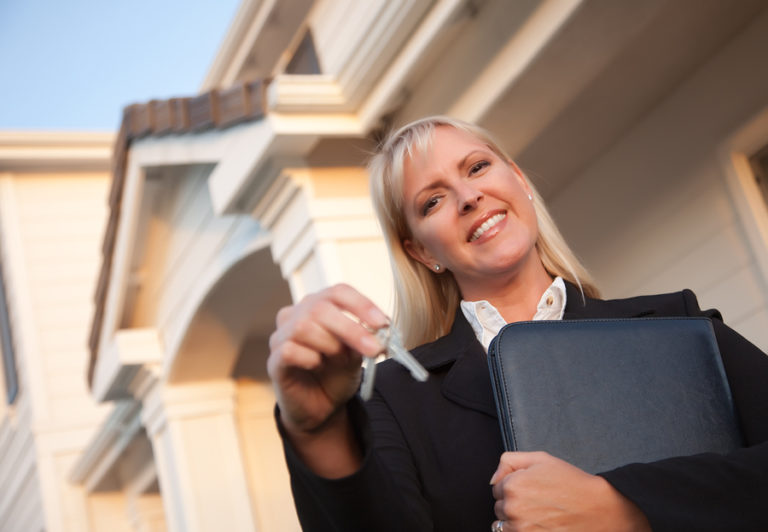 A Realtor dangling a set of keys in her hand.