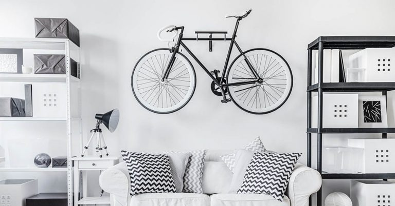 A bike hangs above a white couch in a sleek black-and-white apartment.