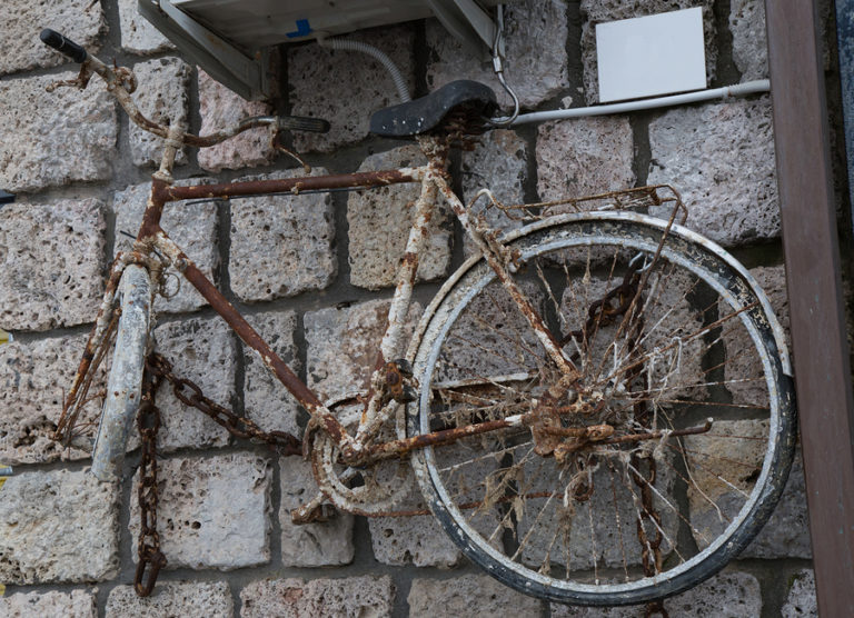 A rusty old bike hanging on a brick wall.