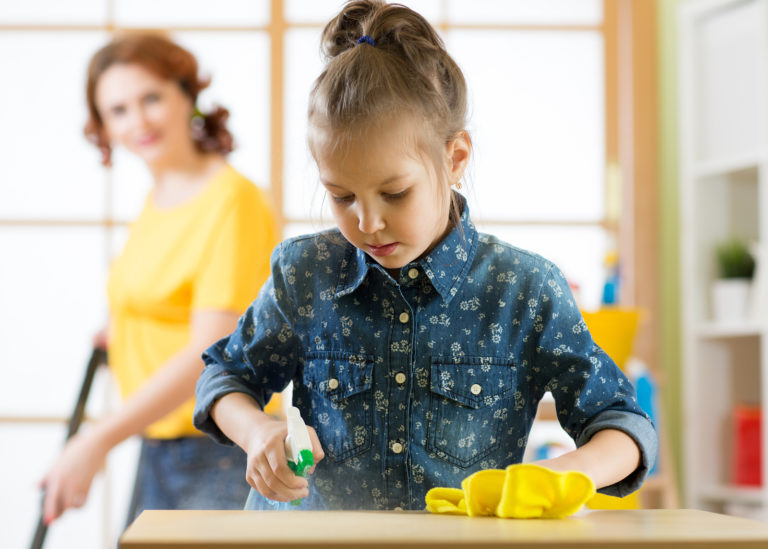 A mother and her young daughter do chores together at home.